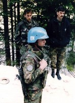 A Dutch UN peacekeeper standing near two unidentified Bosnian men in Srebrenica in 1994.